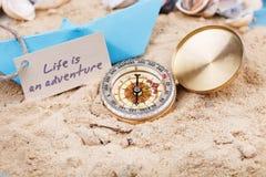 kompas in het zand met teken - het Leven is een avontuur Stock Afbeeldingen