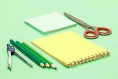Kompas, kolorów ołówki, notatnik, nutowy papier i nożyce na zielonym tle, zdjęcie royalty free