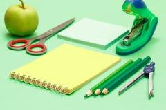 Kompas, kolorów ołówki, notatnik, nutowy papier, zszywacz, jabłko i nożyce na zielonym tle, zdjęcia stock