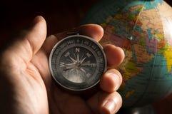 Kompas in menselijke hand met bol stock foto's