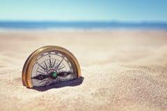 Kompas na plaży z piaskiem i morzem Zdjęcia Royalty Free