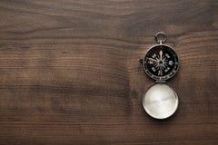Kompas op de bruine houten lijst stock afbeelding