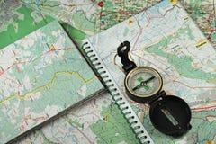 Kompas op de gedetailleerde kaarten Stock Afbeeldingen