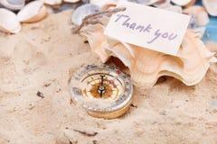 Kompas w piasku z wiadomością - Dziękuje ciebie zdjęcia stock