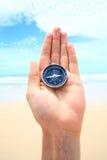 Kompas w ręce przeciw plaży Zdjęcia Royalty Free