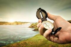 Kompas w ręka podróżniku na linii brzegowej blisko oceanu na tle h Fotografia Royalty Free