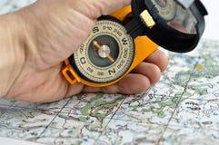 Kompas in zijn hand en een kaart. Royalty-vrije Stock Afbeeldingen