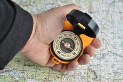 Kompas in zijn hand en een kaart. Stock Fotografie