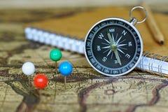 Kompass-, anteckningsbok- och markeringsben på suddighetstappningvärldskartan, resabegrepp Royaltyfri Bild