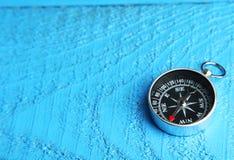 Kompass auf blauem hölzernem Hintergrund Stockfotos