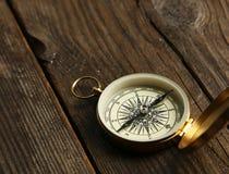 Kompass auf braunem hölzernem Hintergrund Stockbilder
