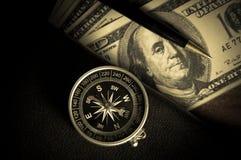 Kompass auf Buch mit Stift und Geld Stockfotografie