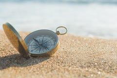 Kompass auf dem goldenen Sand durch das Meer stockbild