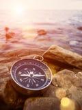 Kompass auf der Bank mit Sonnenaufflackern Lizenzfreie Stockbilder