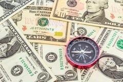 Kompass auf einem Haufen von Papierdollar. Stockfotografie