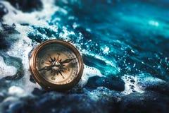 Kompass auf Felsen mit einem bewölkten Himmel lizenzfreie stockfotos