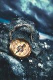 Kompass auf Felsen mit einem bewölkten Himmel stockbild
