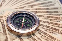Kompass auf Geld Stockfotografie