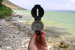 Kompass in der Hand auf dem Naturhintergrund Stockfotografie