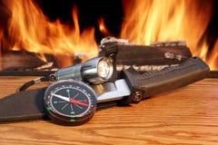 Kompass, en jaktkniv och en handheld ficklampa runt om caen Arkivfoton
