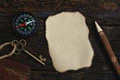 Kompass, gebranntes braunes Papier und hölzerner Bleistift zerknittert an Papierhintergrund, Weinleseton, Reiseplanungskonzept, L lizenzfreies stockbild