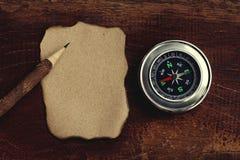 Kompass, gebranntes braunes Papier und hölzerner Bleistift zerknittert an Papierhintergrund, Weinleseton, Reiseplanungskonzept, L stockbild