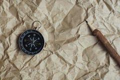 Kompass, gebranntes braunes Papier und hölzerner Bleistift zerknittert an Papierhintergrund, Weinleseton, Reiseplanungskonzept, L stockbilder