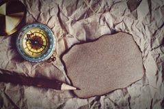 Kompass, gebranntes braunes Papier und hölzerner Bleistift zerknittert an Papierhintergrund, Weinleseton, Reiseplanungskonzept, L lizenzfreie stockbilder