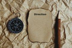 Kompass, gebranntes braunes Papier und hölzerner Bleistift zerknittert an Papierhintergrund, Weinleseton, Richtungstext, Reisepla stockfoto