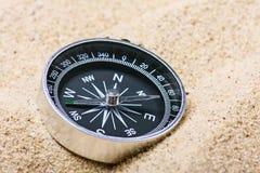 Kompass i sanden Fokus på kompassvisaren Royaltyfri Bild
