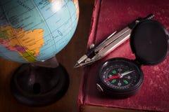 Kompass med jordklotet på den antika boken Royaltyfri Fotografi