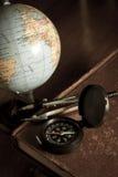 Kompass med jordklotet på den antika boken, stilleben royaltyfri foto