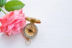 Kompass mit schöner Rosarose auf einem weißen hölzernen Hintergrund Lizenzfreies Stockfoto