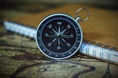Kompass och anteckningsbok på suddighetstappningvärldskartan, resabegrepp Arkivfoton