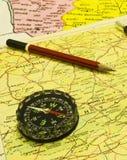 Kompass och blyertspenna över översikter arkivfoton