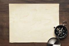 Kompass och gammalt papper på den bruna trätabellen Arkivfoton