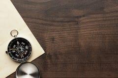 Kompass och gammalt papper på den bruna trätabellen Royaltyfri Bild