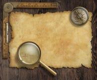 Kompass och loupe för tappning nautisk på tabellen med Fotografering för Bildbyråer