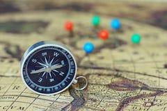 Kompass- och markeringsben på suddighetstappningvärldskartan, resabegrepp, kopieringsutrymme Arkivfoton