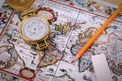 Kompass och penna på tappningöversikt royaltyfria bilder
