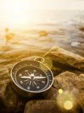 Kompass på kusten på soluppgång Arkivbild