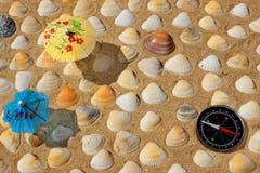 Kompass, paraply och snäckskal Arkivbild