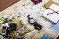 Kompass, Pass, Fotokamera und Blockanmerkungen über Karte Stockfotografie