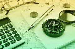 Kompass, Stift, Gläser und Münze auf Notizbuch, erklärendes backgroun stockfoto