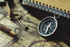 Kompass, tangent, blyertspenna och bok på bakgrund för suddighetstappningöversikt, retro klassisk färgsignal, kopieringsutrymme royaltyfri foto