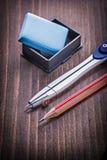 Kompass- und Bleistiftradiergummi auf hölzernem Brett der Weinlese Lizenzfreie Stockbilder