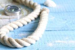Kompass und Seil auf blauen Brettern Stockbild