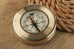 Kompass und Seil auf einem hölzernen lizenzfreie stockfotografie