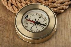 Kompass und Seil auf einem hölzernen stockbilder