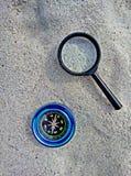 Kompass und Vergrößerungsglas auf Sand stockbilder